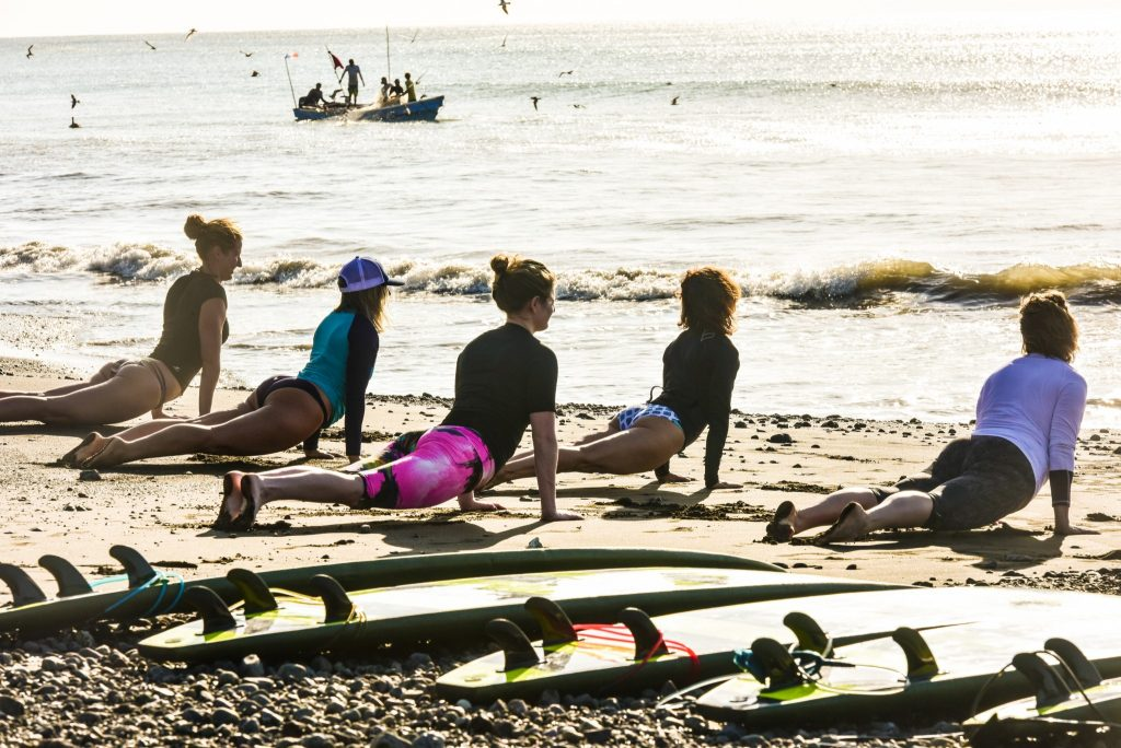A group doing yoga by surf boards