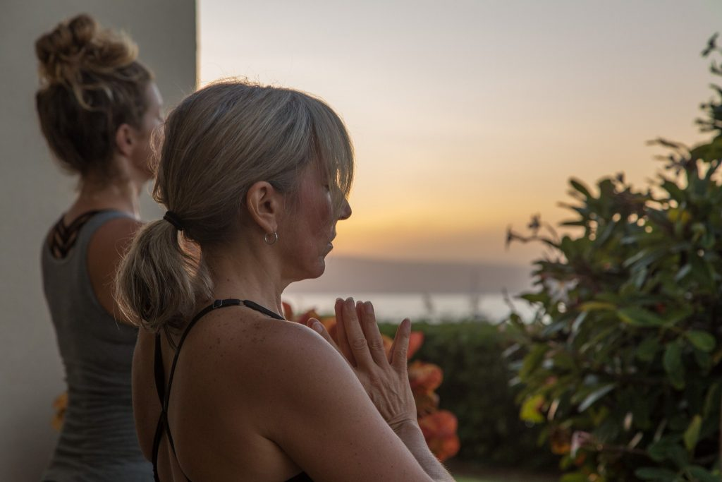 Women meditating and doing yoga at sunset
