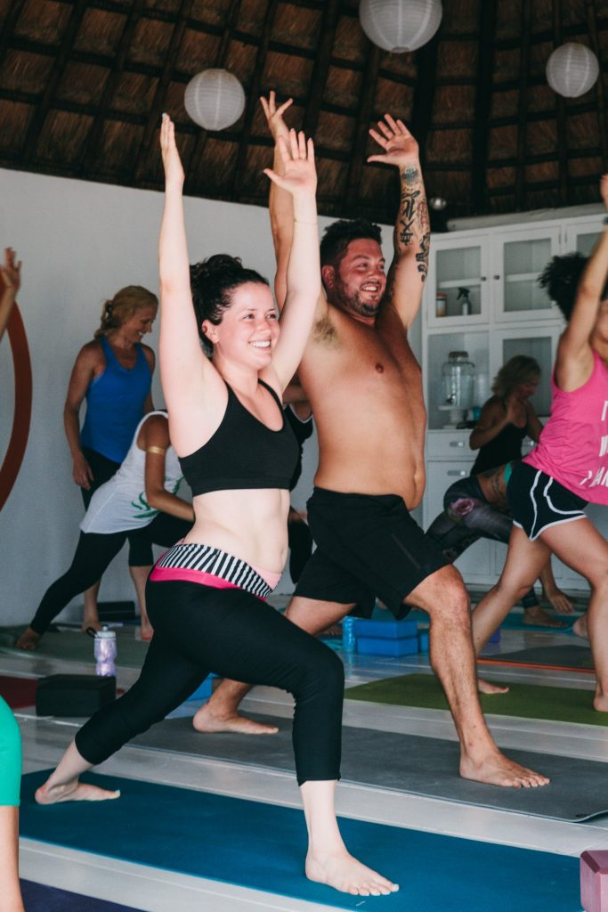Beginner yogis learn to stand in Warrior I